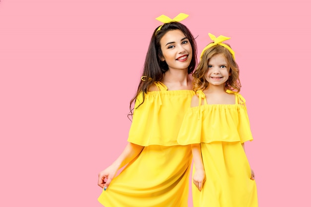 黄色のドレスでポーズをとるかわいい子を持つ若い女性