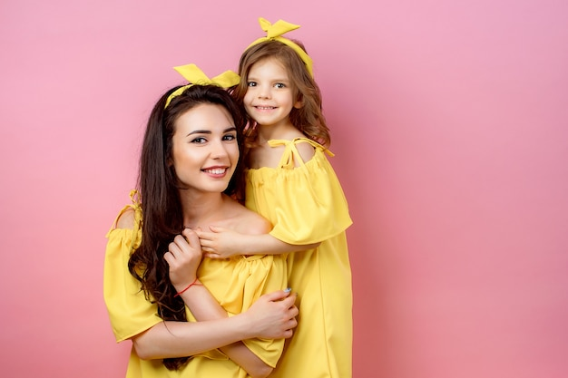 Young woman with cute child posing in yellow dresses