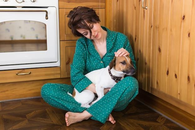 바닥에 앉아 귀여운 강아지 잭 러셀 테리어와 젊은 여자. 애완 동물 및 가정 개념. 머무르다