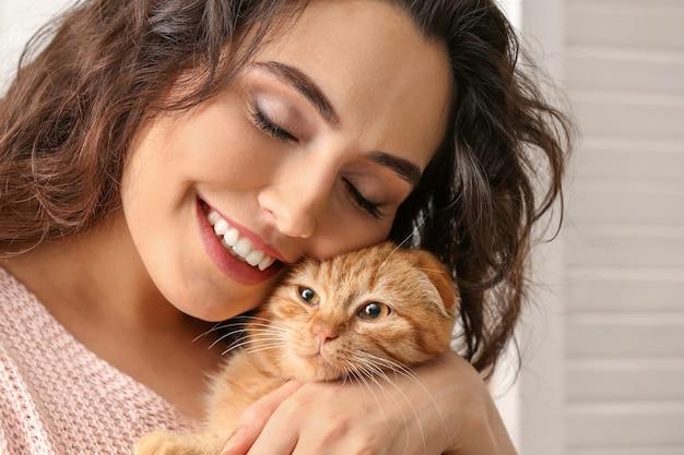 家でかわいい面白い猫と若い女性