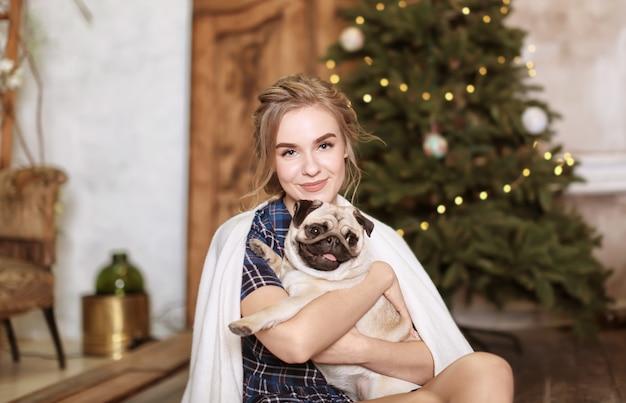 Молодая женщина с милой собакой мопса дома. принятие домашних животных
