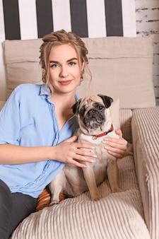 Молодая женщина с милой собакой мопса на софе дома.