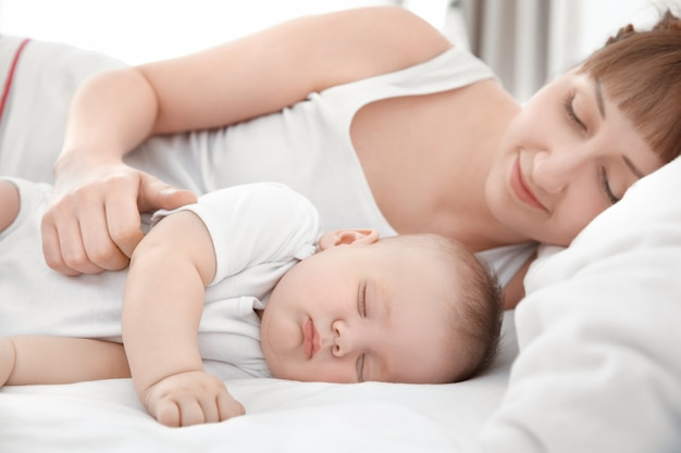 집에서 침대에 누워 귀여운 잠자는 아기와 젊은 여자