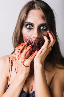 Young woman with damaged face and bloody hands