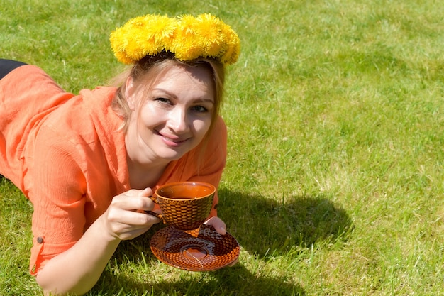 Young woman with a dandelion wreath with a mug of tea on the grass in summer.