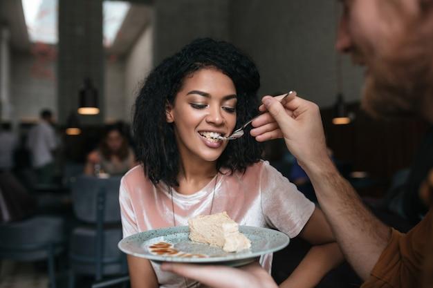 레스토랑에서 케이크를 먹고 검은 곱슬 머리를 가진 젊은 여자 프리미엄 사진