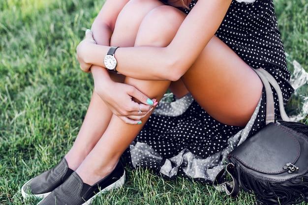 Молодая женщина с темными вьющимися волосами в стильной элегантной черной шляпе позирует в парке
