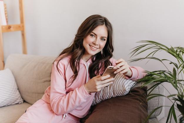 Giovane donna con i capelli scuri vestita con una felpa con cappuccio rosa, è seduta sul suo morbido divano e guarda nuove foto sul suo smartphone