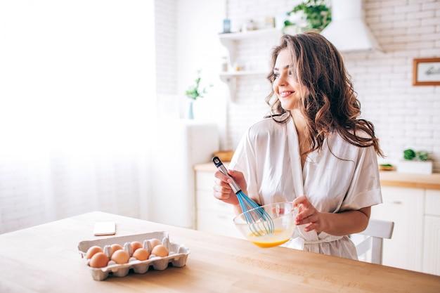 黒髪の若い女性は、キッチンと料理に立ちます。卵を混ぜます。一人で。朝の日差し。まっすぐ見て、笑顔。テーブルの上の電話。