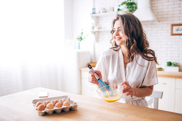 Young woman with dark hair stand in kitchen and cooking. blending eggs. alone. morning daylight. looking straight and smile. phone on table.
