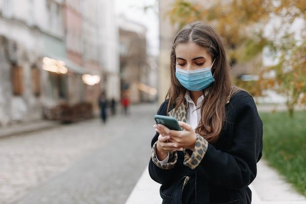 屋外に立って、現代のスマートフォンを使用して黒髪の若い女性。パンデミック時に医療用保護マスクを着用した美しい女性。