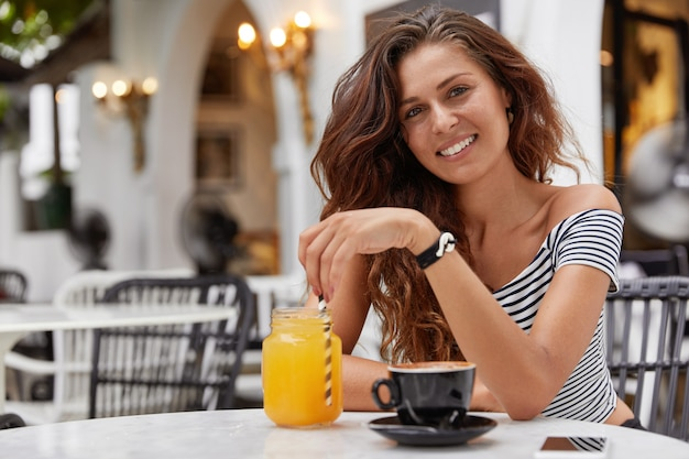 Young woman with dark long hair smiling in a coffee shop