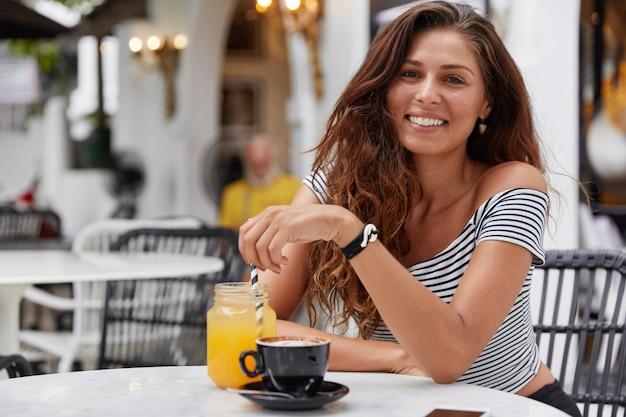 Молодая женщина с темными длинными волосами, улыбаясь в кафе