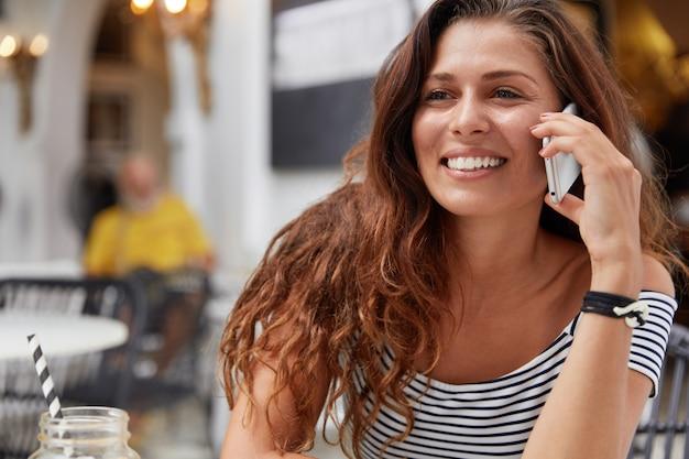 Молодая женщина с темными длинными волосами разговаривает по телефону в кафе