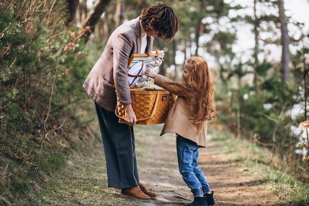 Giovane donna con la figlia nella foresta con scatola da picnic