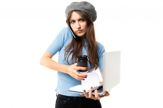 Young woman with delightful smile, long wavy chestnut hair, beautiful makeup, in blue jersey, black jeans, grey beret, standing with laptop, cup of coffe, note, and pen