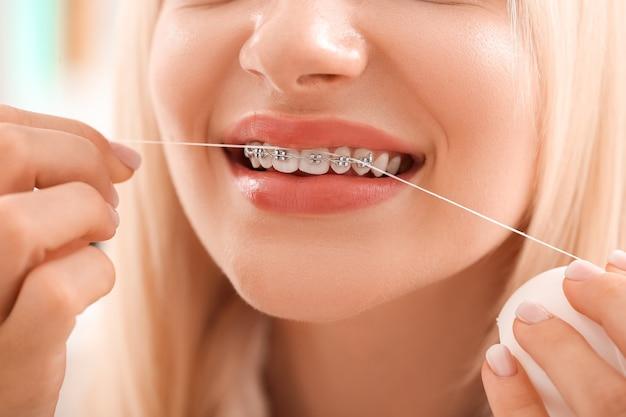 Молодая женщина с брекетами и зубной нитью, крупным планом