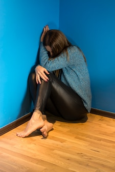 Young woman with depression sitting alone in dark room