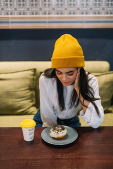 Young woman with dessert on plate near cup of drink at table in cafe