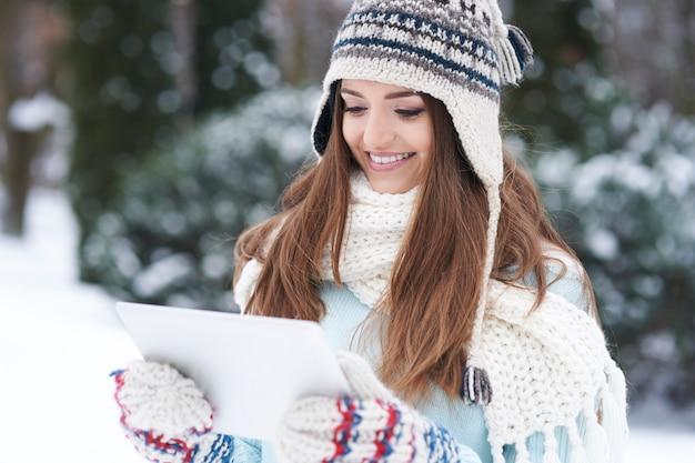 屋外でデバイスを持つ若い女性。