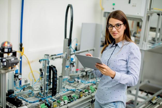 Молодая женщина с цифровой планшеты в мастерской электроники Premium Фотографии
