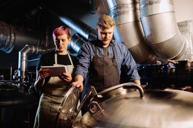 ビール生産の過程で巨大な鋼の貯水槽の蓋を開ける彼女の男性の同僚の隣に立っているデジタルタブレットを持つ若い女性