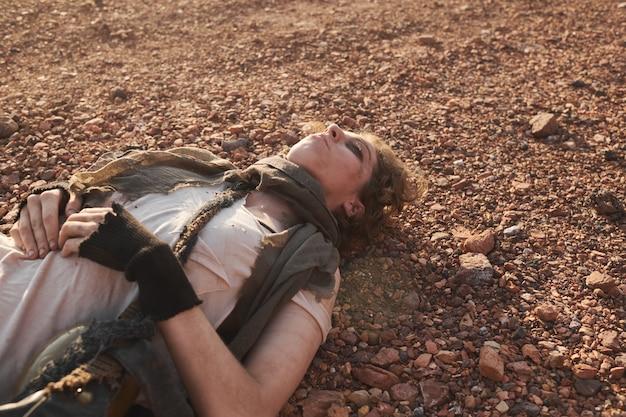 더러운 얼굴과 찢어진 옷을 입은 젊은 여성이 사막에서 눈을 감고 땅에 누워 있다