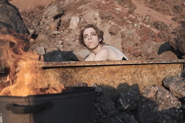 더러운 목욕에 앉아 사막에서 햇빛을 바라보는 더러운 얼굴을 가진 젊은 여자