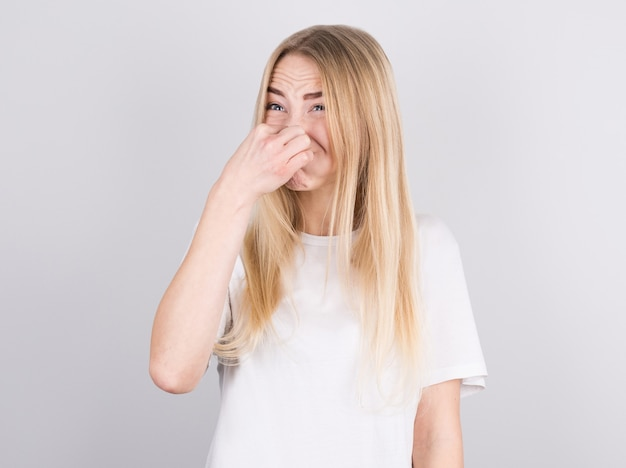 Young woman with disgust on his face pinches nose on white wall. negative emotion facial expression.