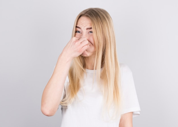 Young woman with disgust on his face pinches nose on white wall