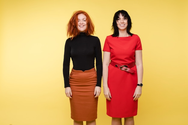 노란색 스튜디오 배경에서 격리된 충돌 후 흐트러진 머리를 한 젊은 여성. 두 패션 여자 친구 또는 긍정적인 감정을 가진 세련된 사업가