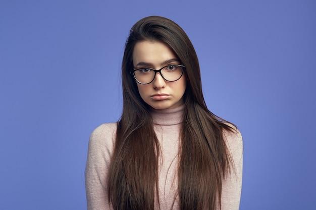 Молодая женщина с недовольным выражением лица кривит губы и смотрит с грустным выражением лица