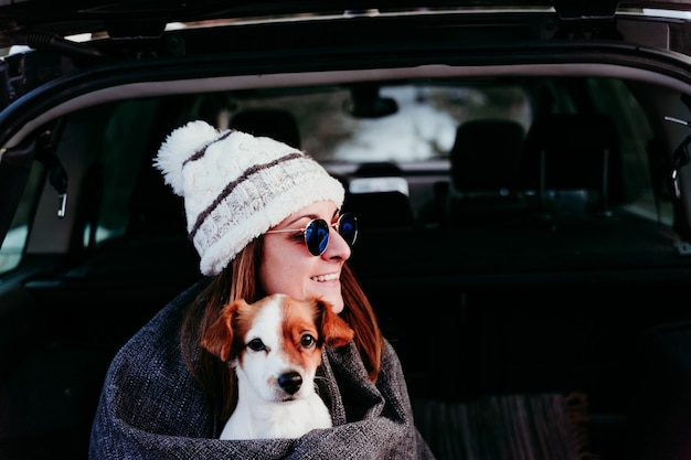 Young woman with dog in car having fun. snowy mountain.