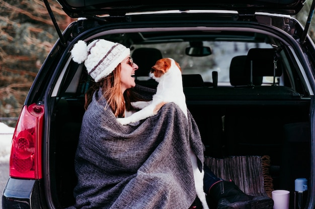 Young woman with dog in car having fun. snowy mountain. Premium Photo