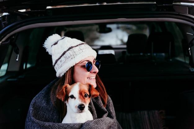 楽しんで車の中で犬と若い女性。雪山。