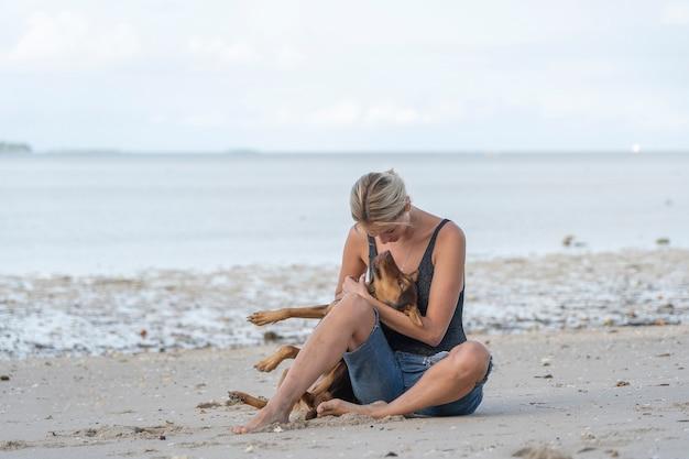 Молодая женщина с собакой возле морской воды на тропическом пляже на острове занзибар, танзания, восточная африка, крупным планом