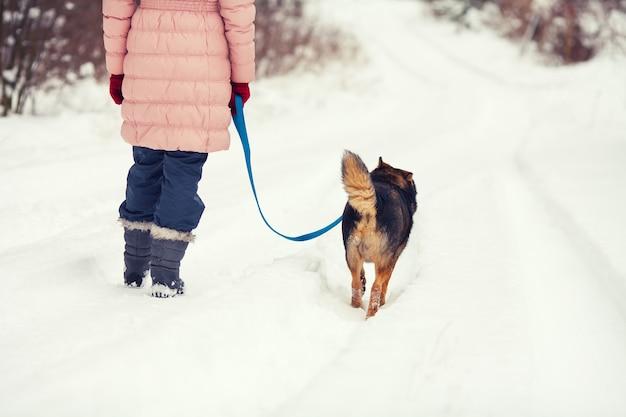 Молодая женщина с собакой гуляет по заснеженной улице обратно к камере