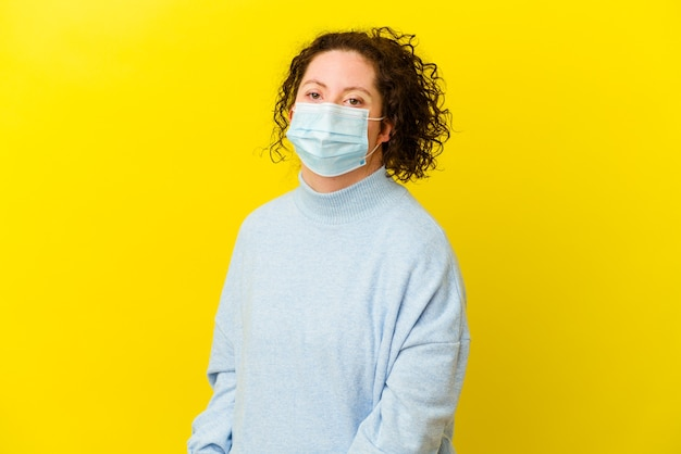 Young woman with down syndrome wearing an antivirus mask isolated looks aside smiling, cheerful and pleasant.