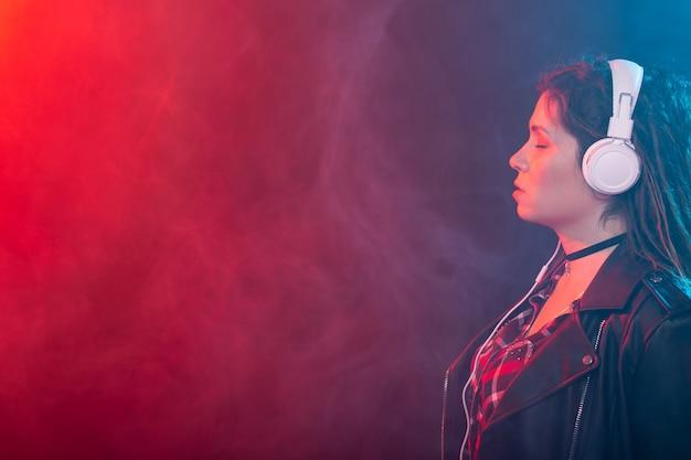 Молодая женщина с дредами наслаждается музыкой в наушниках над красочной стеной с копией пространства