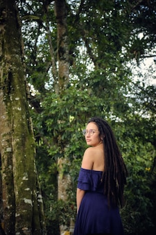 Young woman with dreadlocks on her back and looking towards the camera, she is in a natural forest.