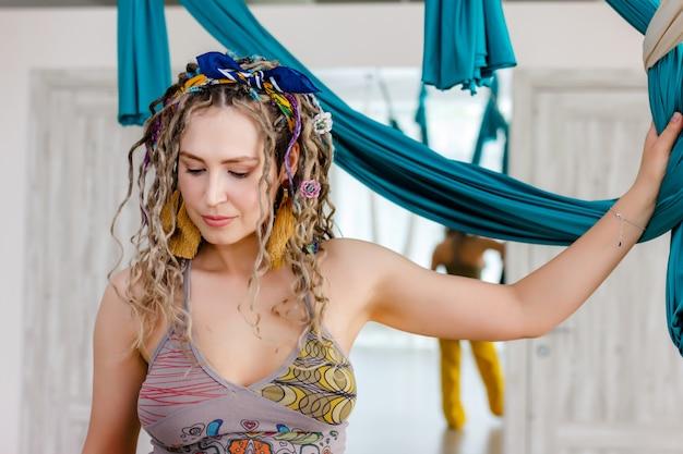 ヨガのハンモックを保持しているドレッドヘアを持つ若い女