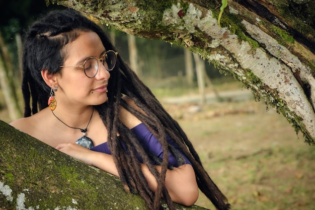 Young woman with dreadlocks, resting her arm on a tree and with her eyes closed. resting and thinking.