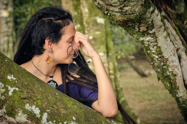 Young woman with dreadlocks, resting her arm on a tree, with her glasses in her hand. she seems to be tired and need a rest.
