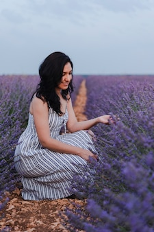 Young woman with a dress admiring lavender