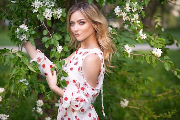 Молодая женщина в платье в цветочном саду
