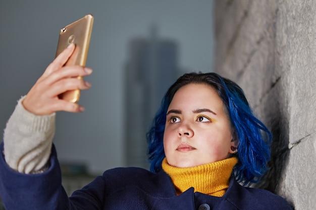 파란 머리카락과 같은 색의 코트를 입은 젊은 여성은 스마트 폰을 사용하여 셀카를 찍거나 저녁에 야외에서 동영상을 촬영합니다.