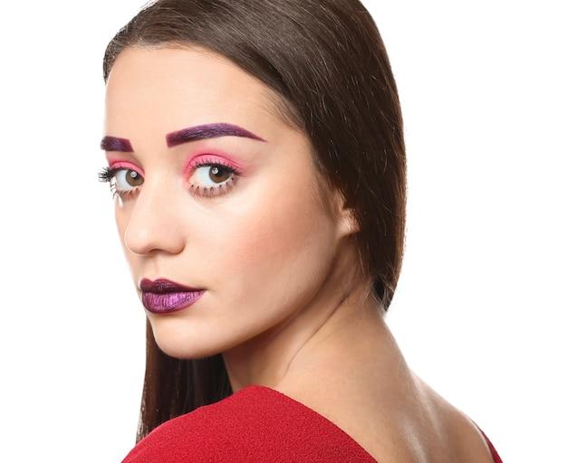 染められた眉毛と白い表面に創造的なメイクの若い女性