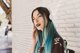Young woman with dyed hair listening music on headphone