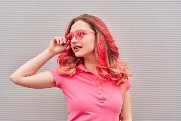 염색 된 핑크 헤어 스타일과 선글라스는 회색 배경에 미소를 가진 젊은 여자