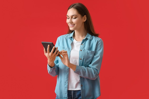 色の電子書籍リーダーを持つ若い女性